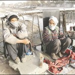 Two members of the Hazara ethnic minority rest between jobs pulling cargo carts in Kabul. Hazaras have long been relegated to menial jobs. (Pamela Constable)