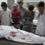 Pakistani Shiite Muslims mourn next to a