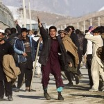 Afghan protesters gesture towards police in Kabul