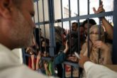 An International Organization for Migration officer talks to Iraqi and Afghanistan asylum seekers after officials said overcrowding was partly to blame for the mass escape.?(JG Photo/Safir Makki)