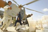 Above: A local boy helps unload ballot materials from an Mi-17 helicopter in the Jaghuri, Afghanistan, for the 18 September elections. Many of the Hazara people who have claimed asylum in Australia were born in this district; those who remain experienced significant difficulties casting a vote. ISAF photo/ Joseph Swafford