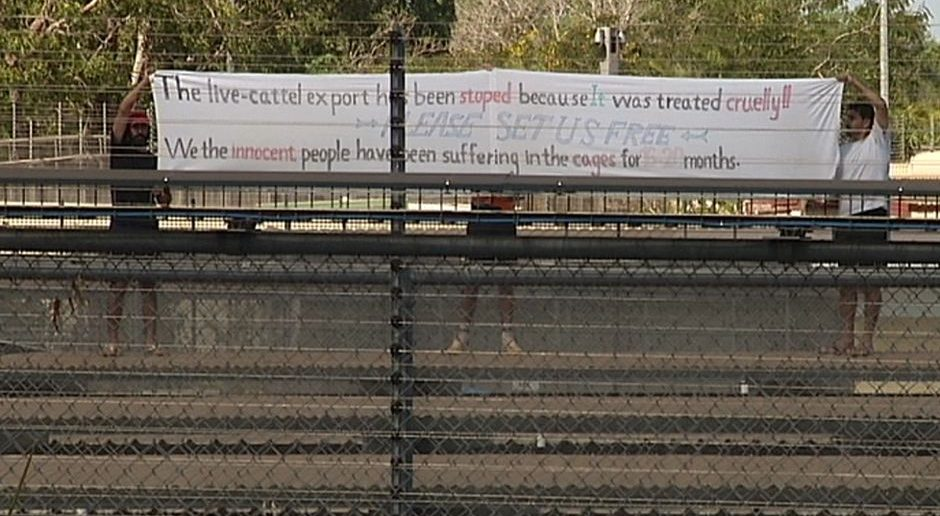 PHOTO: Protestors wave a banner at the Darwin immigration detention centre. (ABC TV)