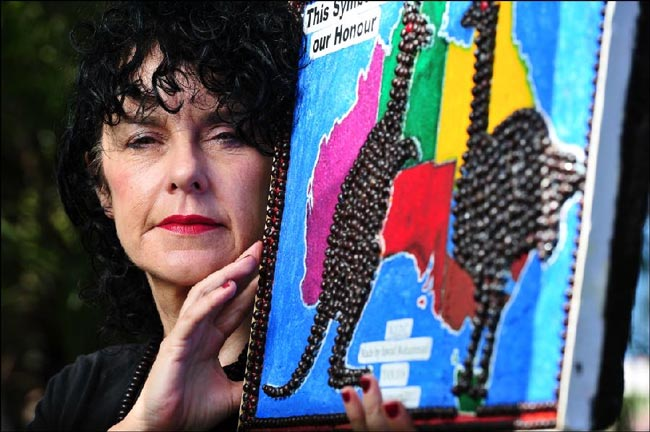 Curator of the Footprints of my Heart exhibition Vikki Reily with some of the artwork by asylum seekers that will be on display at the Darwin Supreme Court. Picture: MICHAEL FRANCHI