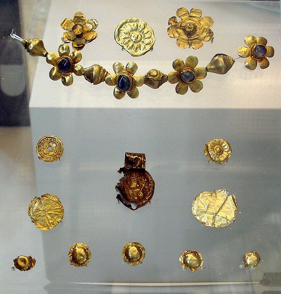 "Offerings found in Bodh Gaya under the ""Enlightenment Throne of the Buddha"", with a decorated coin of the Kushan emperor Huvishka, 3rd century AD. British Museum."