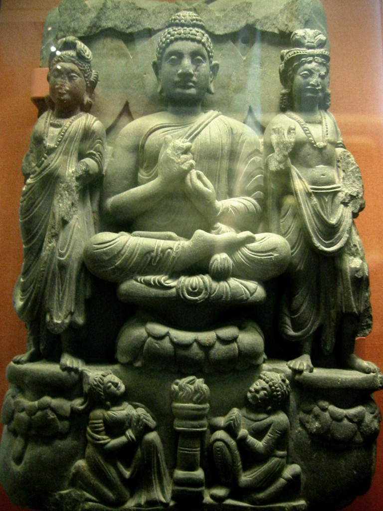 Buddha triad and kneeling Kushan devotee couple. 3rd century