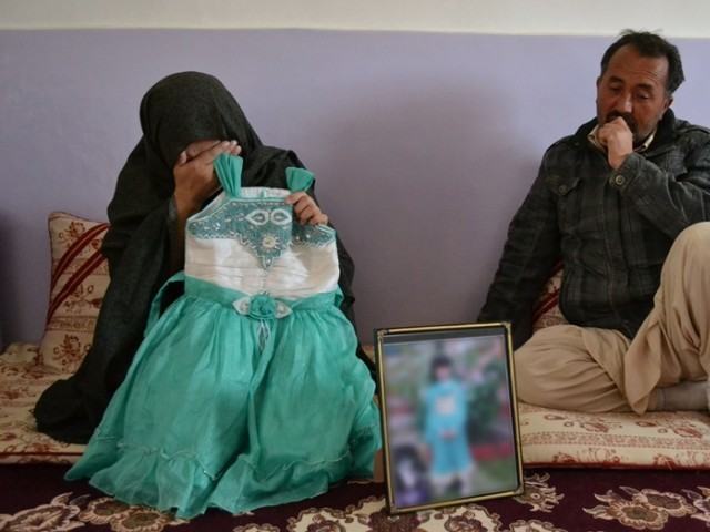 Bakhtawar, the mother of Sahar Batool, who was from the Hazara community and found dead at a garbage dump, shows a photograph of her late child in Quetta on November 7, 2014. PHOTO: AFP