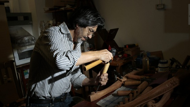 Afghan refugee and craftsman Hashmat Shafaq working on a table leg in his store Rosewood Furniture in Woden. He was a woodworker in Afghanistan before he came to Australia in 1999. Photo: Jeffrey Chan